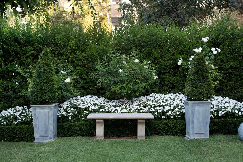 """שיחים גזומים בכדים ובאלמנטים המיובאים מחו""""ל וצמחיה פורחת בצבע לבן, צילום: יעל אילן"""